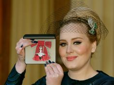 Adele receives MBE Honour from His Royal Highness Prince Charles at Buckingham Palace wearing a Philip Treacy veil with diamond details.
