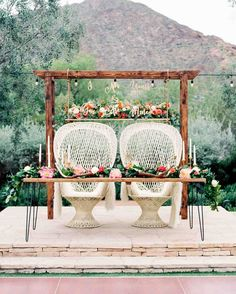 A Bright Wedding in Arizona with Boho Touches | Martha Stewart Weddings - Inspired by a picture, Aubrey knew what she wanted for her sweetheart table and the team created a set-up that reflected her vision. Dang Fine Rentals built the custom wooden structure that went above the table, which also boasted the couple's favorite worship song lyric, laser cut by Happily Ever Etched. Floral adornments, peacock chairs, candles, and colorful blooms finished off this regal sweetheart table.