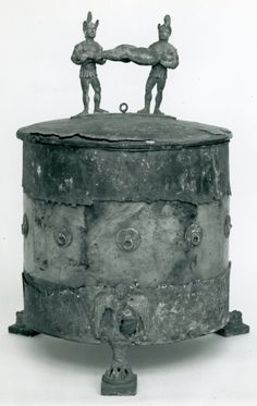 Bronze casket (cista) with Achilles (Achle) sacrificing the Trojan prisoners before Patroclus' pyre. The handle is cast in the form of a satyr and maenad. The feet have lion's paws surmounted by a winged boy, probably Eros, in low relief. Ladies' toilet articles were kept in such caskets. Etruscan.  © The Trustees of the British Museum