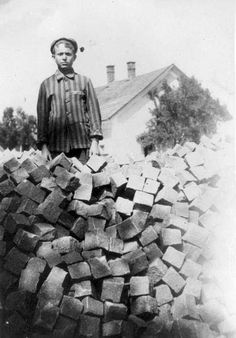 Mauthausen, Austria, A Child in Striped Prisoners' Uniform, Standing Behind a Pile of Bricks