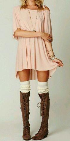 Vestido rosa corto con botas marrones y calzas blancas por encima de las rodillas.