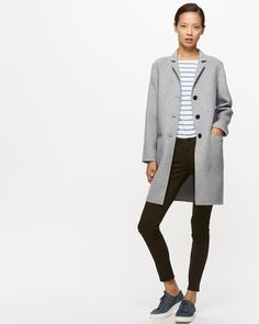 A key coat for the season. This design has been finished by hand and is made from a premium double-faced wool mix, a construction which features two layers of combined fabric so the garment is as beautiful inside as it is on the outside. Perfectly proportioned, the sleeve finishes on the wrist crease, while the hem is cut to mid-thigh. Wear layered over an oversized jumper, trackpants and trainers for a sports-inspired look.
