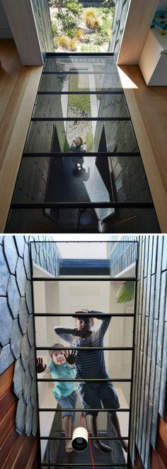 In this modern house, there's a section of the floor that's perforated to look down to the lower floor and to allow sunlight from the tall vertical window to fill the space. Metal Deck, Metal Floor, Glass Floor, Grey Slate Tile, Black Window Frames, Basement Windows, Black Fireplace, Grey Flooring, Floors
