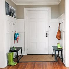 After: Two benches, 10 wall hooks, and a shallow ledge provide storage aplenty on a backdrop of classic double-panel wainscoting. for 104 bucks.  Their solution: Make the most of the foyer's ample wall space by using it to create a makeshift mudroom.