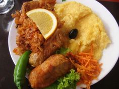A plate of sărmăluţe cu mămăligă, a popular Romanian dish of stuffed cabbage rolls (sarmale), accompanied by sauerkraut and mămăligă. The cabbage rolls are usually garnished with sour cream, not lemon and olive. Cabbage Rolls Recipe, Winter Dishes, Romanian Food, Romanian Recipes, European Cuisine, Christmas Dishes, Christmas Meals, National Dish, Eat To Live