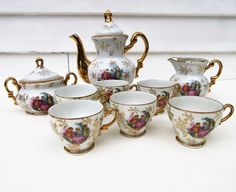 Gorgeous vintage tea pot set includes the porcelain gold trim teapot and matching sugar bowl, creamer and 6 demitasse cups. Each piece in this tea set is gold encrusted and has a depiction of a Victorian courting couple. The illustration from Fragonard's romantic collection is only on the front of each piece. The white porcelain is also decorated with a wispy flower, branch and leaf stencil. Each piece is in very good vintage condition with minimal wear of the gold and no chips or cracks. It…