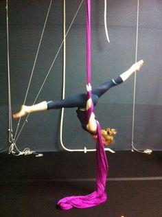 Redhead upside down on circus silks.