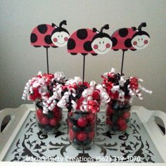 Delightful Ladybug themed centerpieces for a little girl's birthday party. Each ladybug is hand painted and inserted into a glass vase with red and black candies. By Maria's Party Creations of Norwalk, CA.