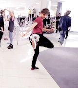 In the backround Lou is doing Niall's hair while Louis kicks a ball
