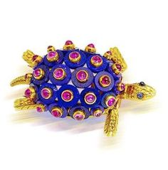 A lapis lazuli, ruby and sapphire tortoise brooch, by Cartier, circa 1965 The shell formed of polished lapis lazuli discs, each with applied cabochon ruby highlight, the head with cabochon sapphire eyes, the legs and tail with textured detail, signed Cartier Paris, numbered, maker's mark, French assay marks, length 3.8cm., maker's case.
