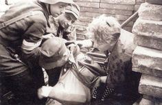 An insurgent is helped out of the sewer exit at ul. Warecka.