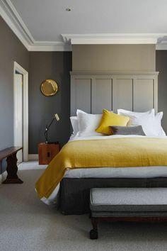 une chambre à coucher élégante en gris et taupe, linge de lit couleur ocre