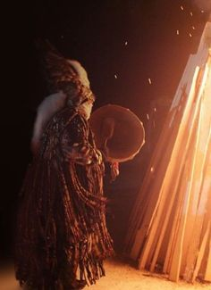 Siberian shaman woman saying prayers to the ancestors before the fire is lit