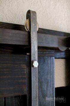 diy barn door rolling hardware on a black barn door - Baby Rabies
