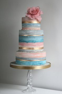 Pastel watercolor cake with gold accents and rose topper.