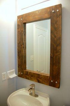 DIY rustic wood mirror hanging over sink in grey half bathroom