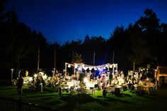during twilight, guests and family party at the reception during a warm evening wedding at their pema osel ling buddhist retreat center wedding in the santa cruz redwood mountains in corralitos, ca