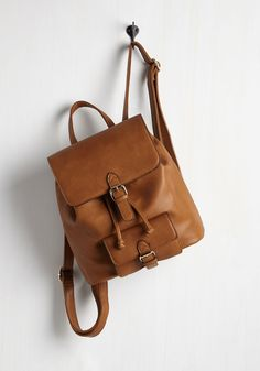 With time to spare between classes, you take a quick spin through the campus park to show off this cognac brown backpack! This faux-leather bag flaunts adjustable straps, a pull-tie closure under its glistening, golden buckles, and plenty of pockets in which to store the day's worth of snacks.