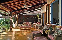 A varanda, com sofás e poltronas, serve de extensão da sala. Ela protege contra o sol, a chuva e o vento, além de manter agradável a temperatura interna da casa. Com inclinação de 35%, o telhado cria uma grande área de sombra na fachada. Projeto de Lydia Garcia e Bianca Farinazzo.