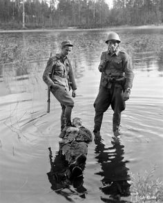 Finnish soldiers stand in lake Paanajärvi over the dead body of an enemy Soviet soldier killed during the Finnish-Soviet Continuation War. Near Rukajärvi, karelia, Finland (now Rugozero, Republic of Karelia, Russia). 31 July 1941.