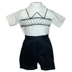 Eton Suit (Navy) - Traditional smocked boys 2-piece suit. The coloured shorts compliment the piping and smocking to the top. The pleated trousers attach to top with fabric matched buttons and have elasticised legs. Available in sizes 6 months - 4 years.