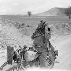 A motorcycle despatch rider putting on his gas mask during a 50-mile motorcycle trial in Cyprus, 3 March 1942.