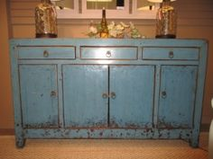 """70452 Paleo Sideboard Price: $799.99  Item #: 40957 What a stunning color! This distressed blue sideboard has four doors and three small drawers on top. This antique piece is made of solid wood and could be utilized in a dining or living room. Measurements are 62"""" long x 18"""" deep x 37"""" high."""