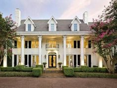 Large traditional Colonial Georgian Plantation two-story tall columns Landscaped with low foundation shrubs Boxwood  formal landscape