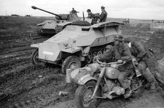 German soldiers on a BMW motorcycle ride past a Sd.Kfz. 251 half-track and a Panther tank from the 5th SS Panzer Division on the Eastern Front
