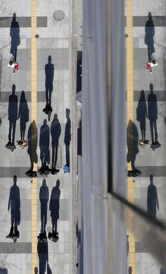 Japanese shadowgraphs. Pedestrians cast shadows on the sidewalk near the headquarters of the Bank of Japan in Tokyo.  Ombres japonaises. Le...