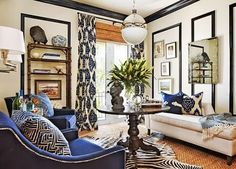 Love the layered, textured, exotic vibe in this room by Barclay Butera. Off white walls and black millwork and moulding play perfectly with navy patterned draperies and pillows, tons of grasscloth and