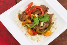 Easy Pepper Steak: A quick saute of marinated sirloin, red and green bell pepper, onion and garlic - served over steamed white rice.