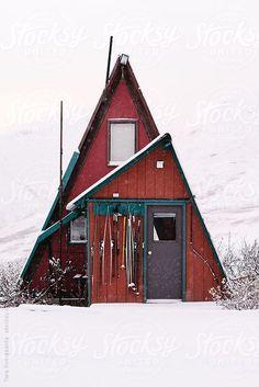 A-frame cabin in Alaska in the snow by Tara Romasanta