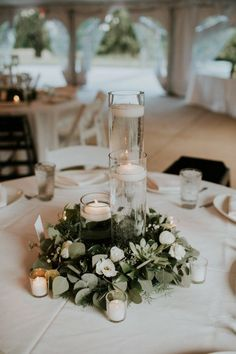 Garden Wedding Centerpiece Inspiration | Looking for something simple and cost effective? Use tall cylinder vases with floating candles and add a wreath of greenery around them to create a look that is simple and chic.
