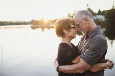 Content middle aged, retired couple hugging together outside on lake ocean dock by robcampbell | Stocksy United