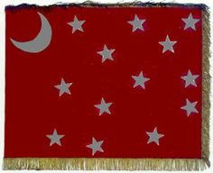 "Flag of the 9th Texas Cavalry. Pvt. Sparks of the 9th described the flag as ""a small brownish red silk flag, in the center of which was a crescent moon and thirteen five-pointed silver stars. It was trimmed with silk fringe and was attached to a dark mahogany colored staff with a gilded spear head at the top"". Author Howard Michael Madaus notes the 27th Ohio captured an ""unmarked Van Dorn pattern battle flag of the 9th Texas Cavalry"" in Oct 1862 in the battles in and around Corinth…"
