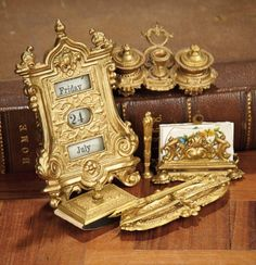 """2 1/2"""" (6 cm.) l. inkwells, 4""""h. calendar. The gilded metal desk accessories with elaborate pressed designs include a double inkwell with candle holder and pen holder with pen, letter holder, letter opener in the shape of sword and with tray; blotter, and perpetual calendar with windows for revolving day of the week, date of the month, and month. Excellent condition. Late 19th century."""
