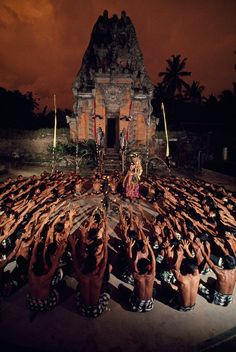 Seated villagers wave arms as they enact a play in front of a temple in Bali, Indonesia, 1969. Photograph by Donna and Gilbert M. Grosvenor, National Geographic Creative