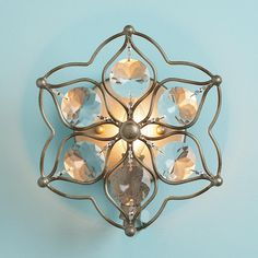 "Sconce for toilet area: Crystal Flower Sconce 9"" h x 9"" w x 4"" D one 60 watt, Clear round faceted crystals are used to make the petals in this wire floral frame finished in a unique combination of silver and gold we call Champagne. $149"