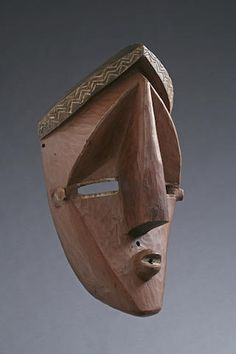 A Lwalwa facemask Democratic Republic of Congo, dramatically carved in highly abstracted form accentuating the repeating planes of the concave face and arching coif. Remains of white in-filling around the eyes, mouth, and coiffure.  height 15 1/2in FOOTNOTES Provenance: From an old Belgian collection  Among the Lwalwa, this particular style of mask is know as Mvondo and is one of the two types of Lwalwa male masks (Felix 1987). The small hole between the nose and mouth was used to secure…