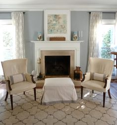 our inviting living room: benjamin moore coventry gray walls, pair vintage wingback chairs, quatrafoil rug, mantel with framed art and antique french blue vases