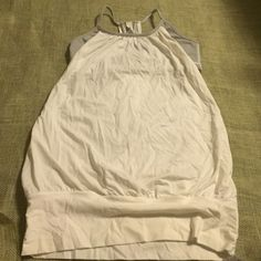 "Lululemon Sports Bra & White Tank Hard to find Lululemon Dual Layer 'Let it Loose' sports bra and white tank.  The sports bra hooked inside of the white tank is white and coal wee stripe.  3 1/2"" hem at the bottom.  Approximately 26"" long.  Excellent condition.  No rips or stains. lululemon athletica Tops Tank Tops"