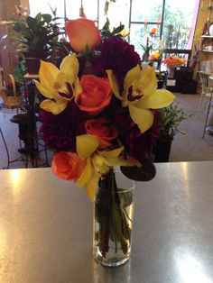 Coral roses, yellow cymbidium orchid blooms and purple dahlias - colors?