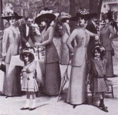 A picture of society includes ladies and children . Ladies wore the long straight skirts , with female's suits and big hats with feathers. The little girls wore skirts whose length were above knee , high socks and got fussy hats too
