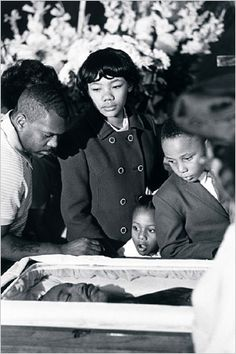 The coffin of the Rev. Dr. Martin Luther King Jr. surrounded by mourners, including his children.
