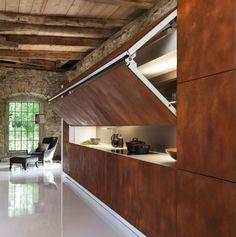 Une cuisine unique en son genre : un large panneau relevable permet de révéler le plan de travail. Rabattu, il dissimule la cuisine derrière une façade au look de métal vieilli.