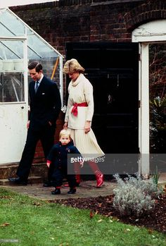 1983--Princess Diana, Princess of Wales and Prince Charles, Prince of Wales watch their toddler son Prince William in the gardens of Kensington Palace on December 14, 1983 in London, England.