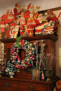 Vintage hutch decorated with a wonderful collection of retro paper Santa's and ornaments.
