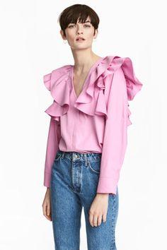 Bluzka z falbanami: Prosta bluzka z bawełnianej tkaniny z dużymi falbanami u góry. Dekolt w serek, z przodu kryte zapięcie. Długie, szerokie rękawy z zakładkami i zapięciem u dołu.