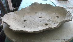 Concrete slab formed bonsai pot with multiple holes for drainage and wiring anchoring points.  These can also be formed by dipping rough cloth like burlap into concrete and draping.